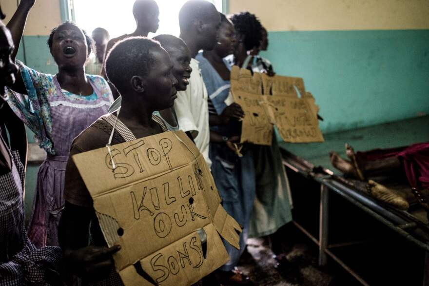 "Friends of Maseno University student Titus Okul, who was killed during a protest the day before, hold placards reading ""stop killing our sons"" as they demonstrate at the morgue on Friday in Kisumu, Kenya."