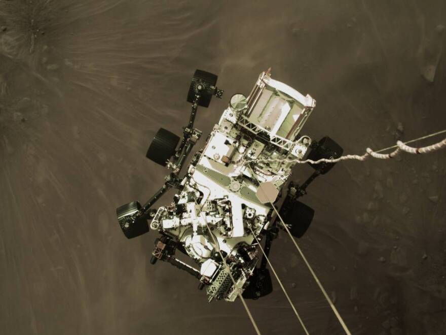 A camera on the descent stage of the Mars Perseverance spacecraft shows the rover being lowered to the planet's surface on Thursday.