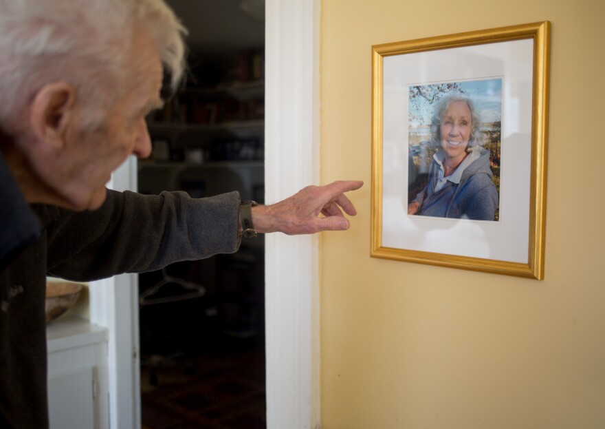 Jack Snow looks at a photo of his late wife, Lyn, on the wall of their home in Thomaston, Maine. Lyn Snow was bitten by a tick in late 2013 and died of Powassan, a tick-borne virus.