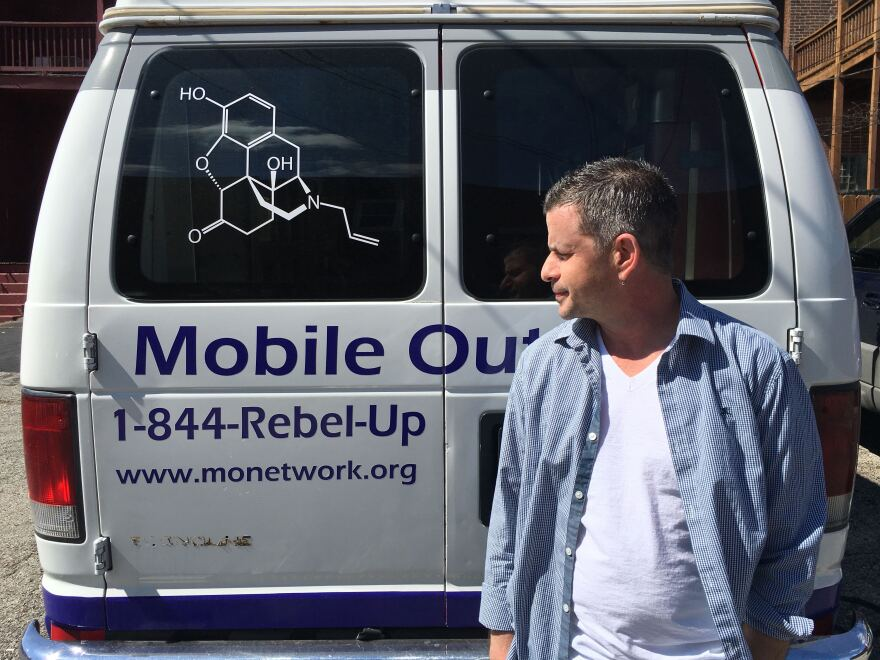 Missouri Network for Opiate Reform and Recovery Executive Director stands beside the nonprofit's mobile outreach van. The decal on the back window represents the molecule naloxone, a chemical that can reverse and overdose.