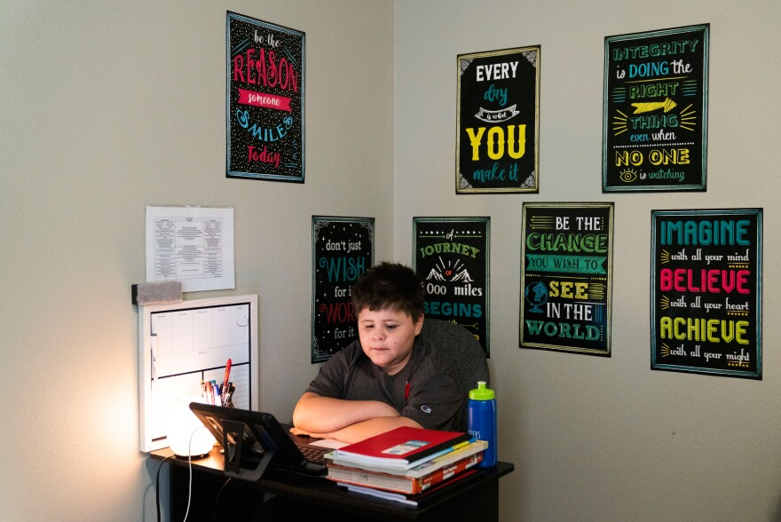 Niko sits at the virtual learning workspace that Barrera set up in his bedroom.