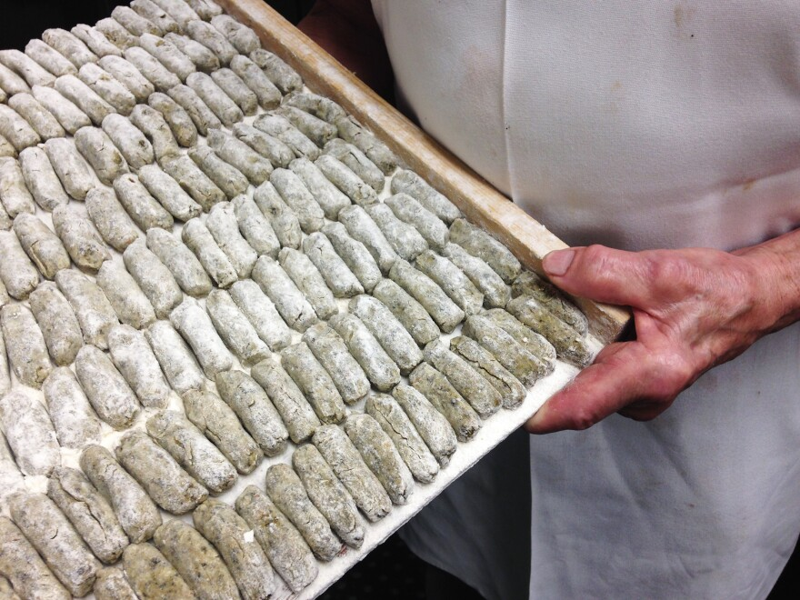 Clemente Cittoni holds a tray of malfatti.