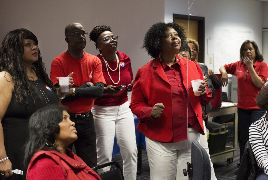 St. Louis Public Schools staffers watch a television news update while waiting for results on Proposition 1 at district headquarters.