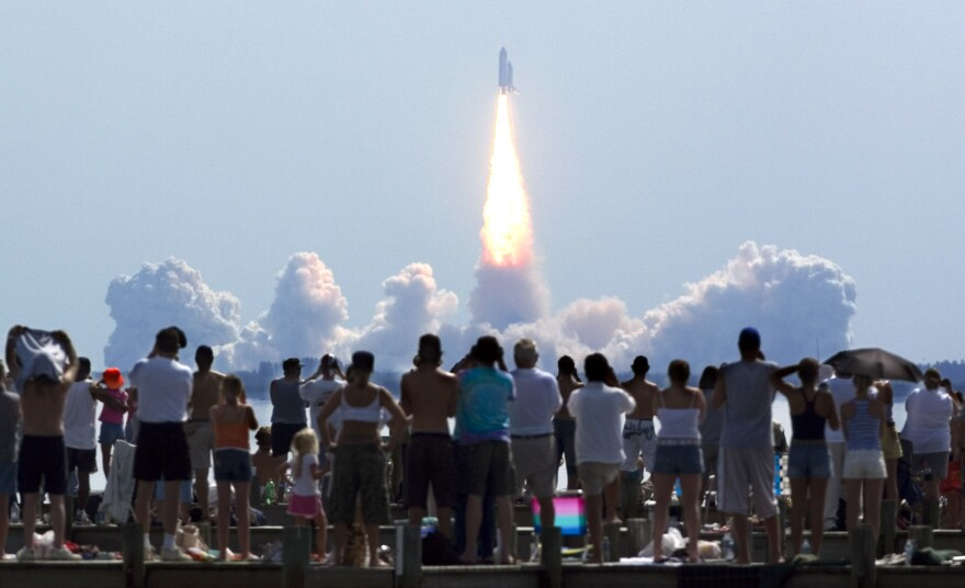 Crowds watch as the Space Shuttle Discovery lifts off from Kennedy Space Center in 2005. NASA is asking people to stay away from this week's launch due to the pandemic.