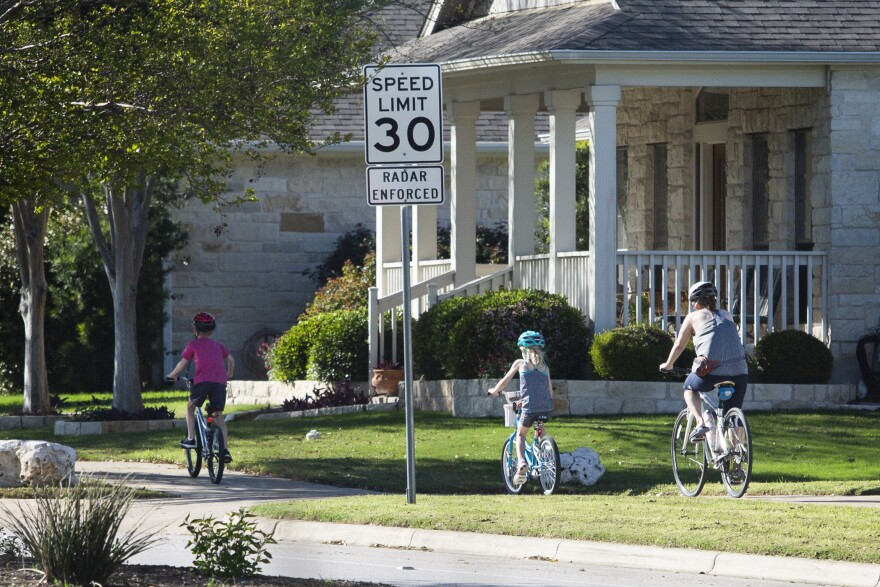 People ride bikes in a Cedar Park neighborhood during the coronavirus pandemic.