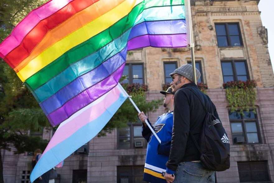 Protesters hold LGBTQ pride flags at a Rainbow Workers' Alliance rally.