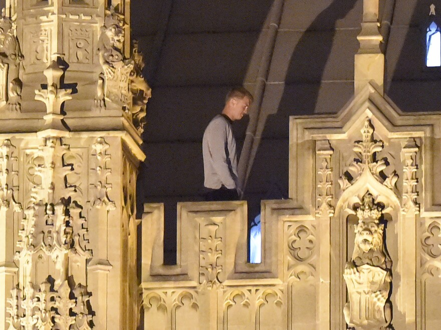 A trespasser stands and walks along the roof at House of Commons early Sunday morning in London. The unidentified man was taken into custody after spending about eight hours wandering around the roof of the Palace of Westminster.