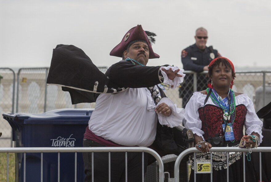 A krewe member dressed like a pirate tosses beads