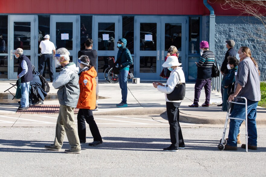 People wait in line for a vaccine from Austin Public Health in January.