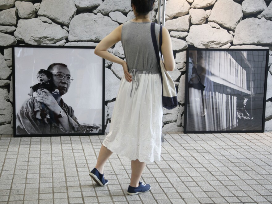 "A visitor looks at Liu Xia's photograph of her husband Liu Xiaobo holding a doll, during the 2012 ""Silent Strength of Liu Xia"" exhibition in Hong Kong. The photographer, painter and poet has been under house arrest for most of the time since her husband was awarded the Nobel Peace Prize in 2010."