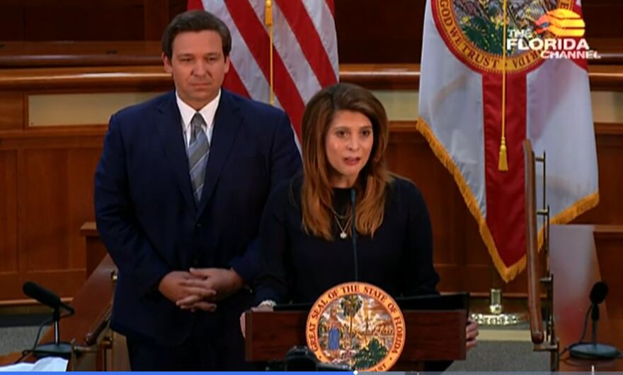Woman speaks at a podium. A man stands behind her, along with flags of the United States and Florida.