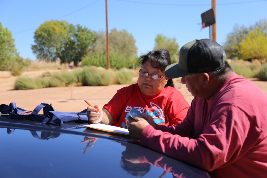 Photo of Dalene Redhorse helping Darryll fill out a voter registration form.