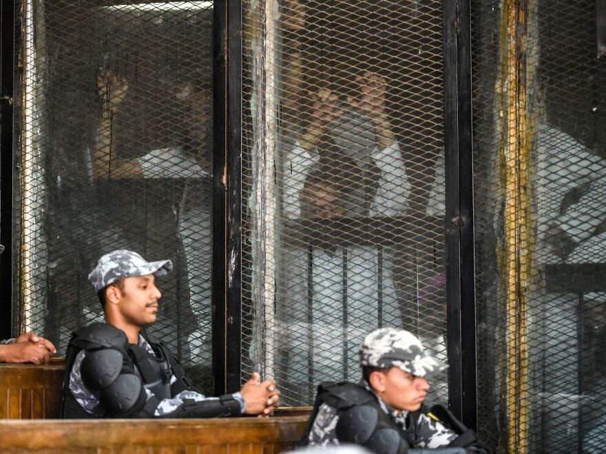 Prisoners including members of Egypt's banned Muslim Brotherhood wait inside a glass dock during their trial in Cairo on July 28. Egypt's courts have held mass trials of hundreds of defendants, sentencing many of them to death.