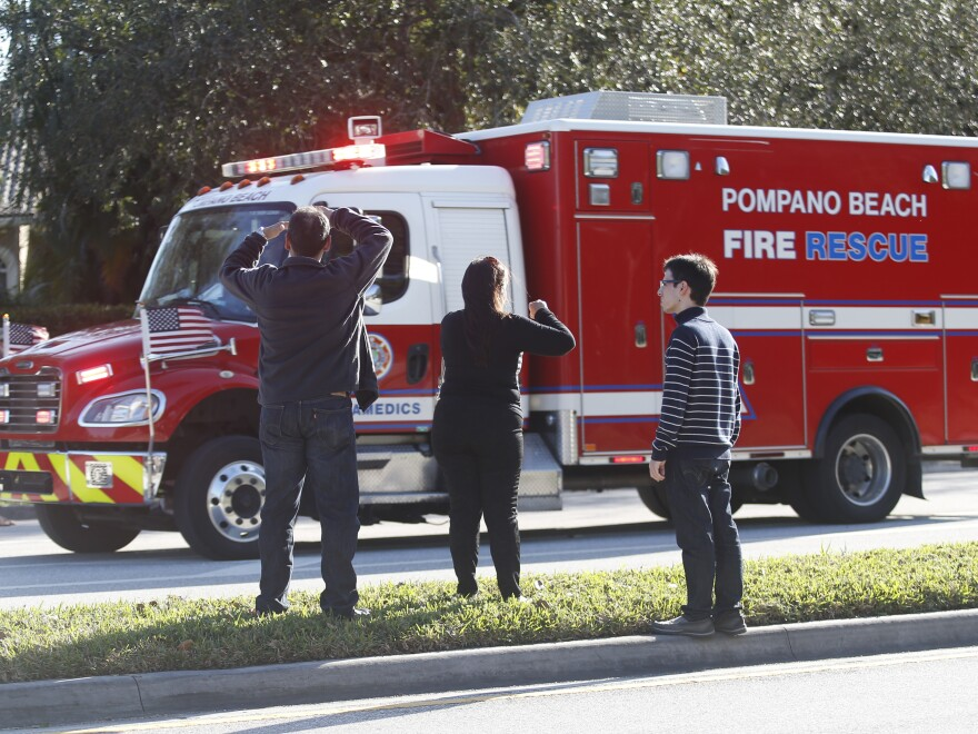Family members watch a rescue vehicle pass by on Feb. 14 in Parkland, Fla.