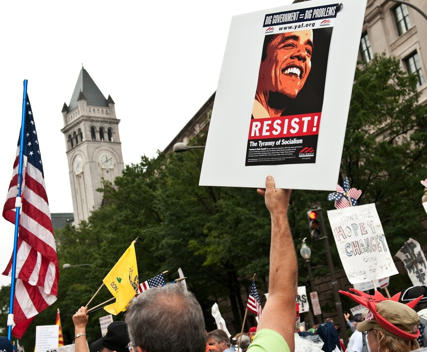 "A demonstrator carries a sign calling people to ""resist"" President Barack Obama perceived socialist policies during a march of supporters of the conservative Tea Party movement in Washington."
