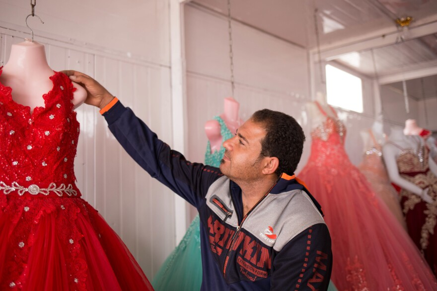 Hussam Assaf adjusts a dress in the rent-a-wedding-gown shop he runs with his wife in the Zaatari refugee camp.