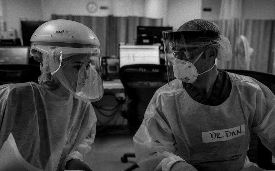 Drs. Katie Ross and Dan Dworkis discuss the care of several patients in the emergency department's COVID-19 unit. The doctors' muffled voices are hard to hear over the sound of air filtration units humming and monitors alarming.