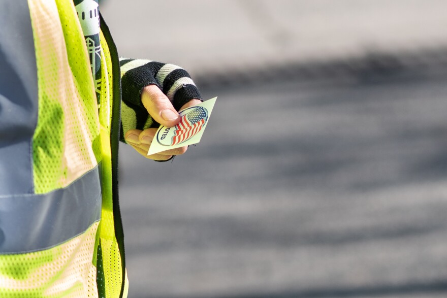 "An election worker wearing a yellow reflective vest and fingerless gloves holds an ""I voted sticker"""