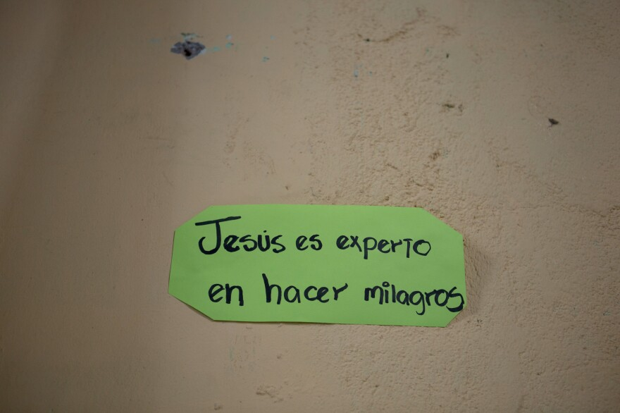 """A sign reading """"Jesus is an expert in making miracles"""" hangs a wall of the Eben-ezer church in a gang-controlled neighborhood in San Salvador."""