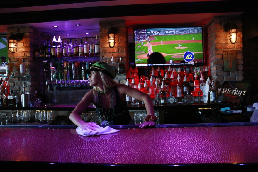 Kelli Rizza cleans the bar before closing the doors of McSorley's Beach Pub at 5 o'clock on Tuesday, March 17, 2020, in Fort Lauderdale Fla. Florida Gov. Ron DeSantis, released a statement saying that all bars and nightclubs throughout Florida will close for the next 30 days.