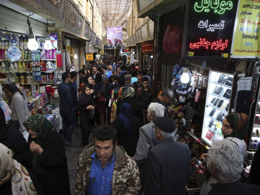 Shoppers make their way in a Tehran bazaar. Once international sanctions are lifted, $100 billion from Iranian oil sales will be released from escrow accounts.