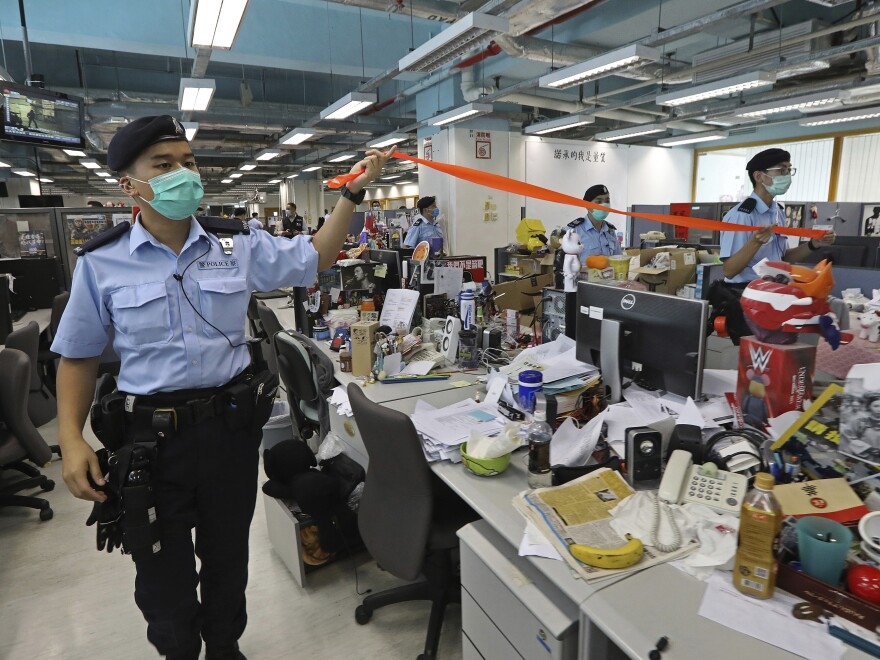 Hong Kong police officers searching the newsroom of the <em>Apple Daily</em> newspaper Monday after arresting the paper's publisher, Jimmy Lai.