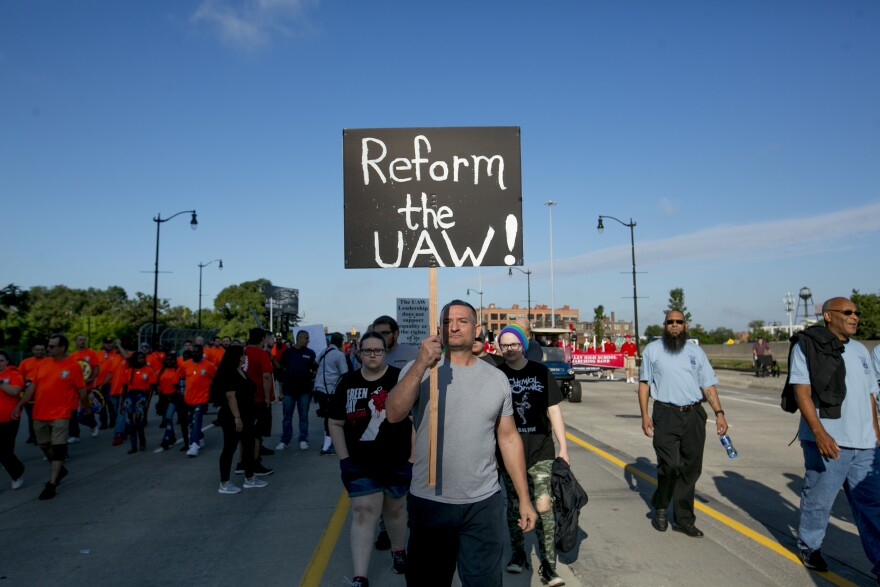 "A United Auto Workers member holds a sign reading ""Reform the UAW!"" during a protest at a Labor Day parade in Detroit."