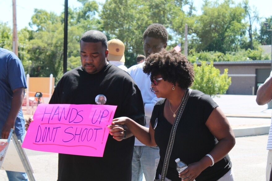 """Sen. Maria Chappelle-Nadal attends a protest holding the hand of a man holding a bright pink sign that reads """"HANDS UP! DONT SHOOT!"""""""