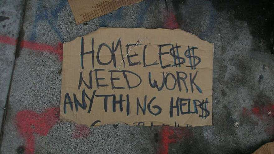 "Sign reading: ""Homele$$ Need Work Anything Helps"""