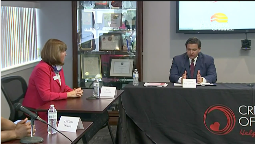 Clara Reynolds, president of the Crisis Center of Tampa Bay, talking with Florida Gov. Ron DeSantis