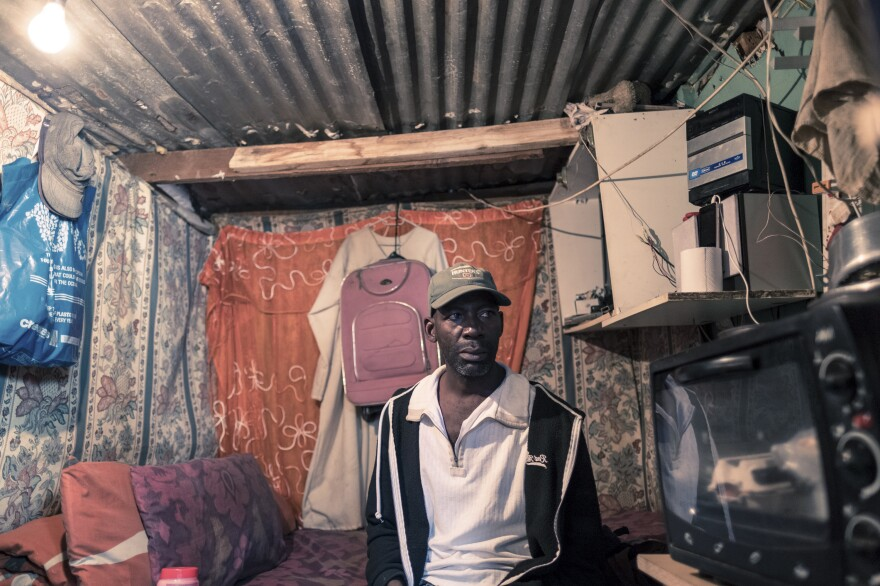 Ishmae Uchani, 47, in his one-room home in the township of Masiphumelele in Cape Town. Uchani shares his house, which measures approximately 6 feet by 10 feet, with his wife and two children. He says the government's orders to stay at home during the coronavirus lockdown are unworkable. Uchani was a day laborer in the construction industry before the lockdown and has now lost his income.