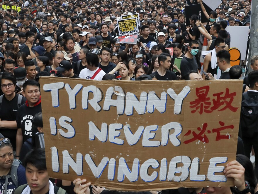 Tens of thousands of protesters carry posters and banners Sunday in Hong Kong as they continue to protest an extradition bill.