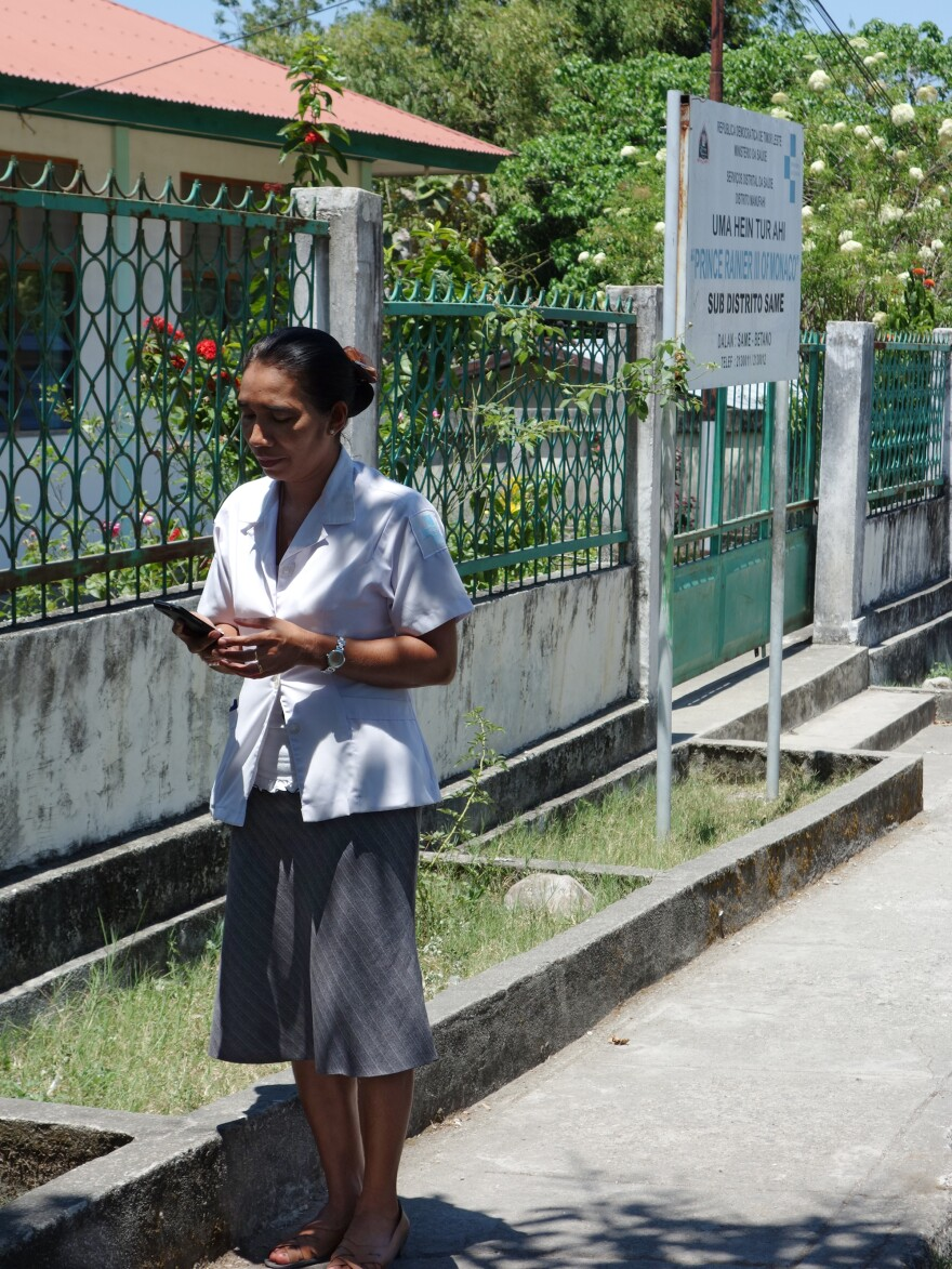 Midwife Mana Justa checks her phone outside the maternity ward in the village Same. The Liga Inan service allows mothers and midwives to send short messages to each other when the mothers have questions.