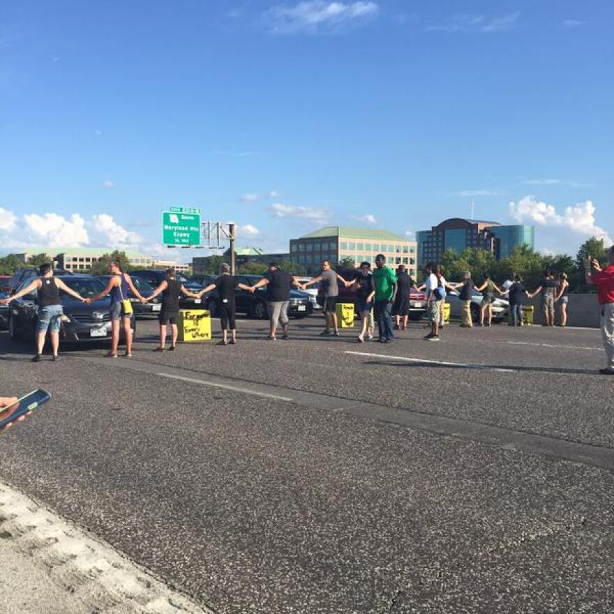 Protesters join hands to block traffic near the Blanchette Bridge on Monday.