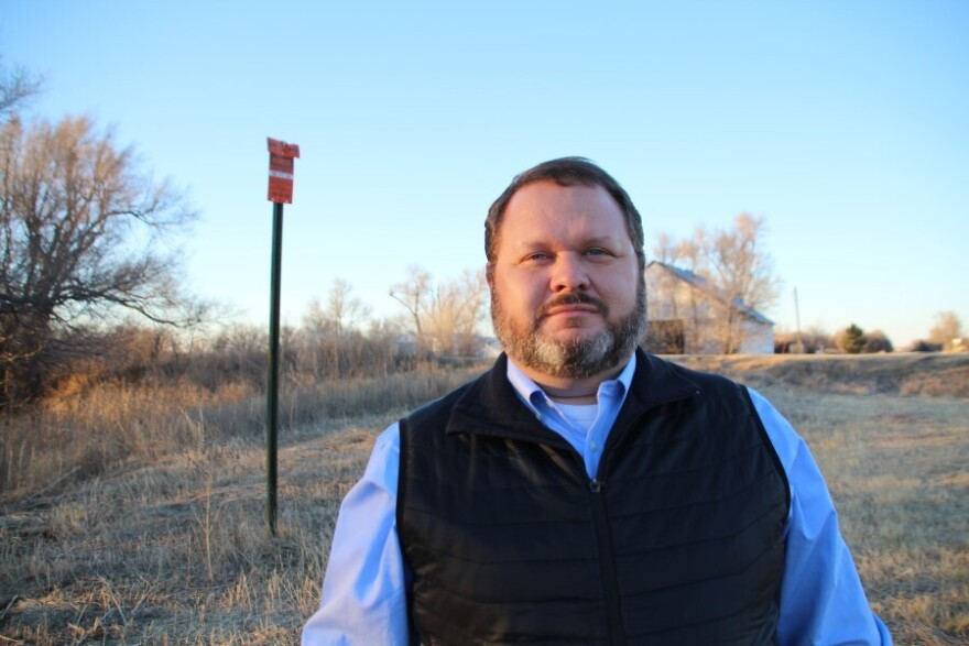 Joey Bahr stands near a sign marking the buried cable that he can't tap into for his home internet, even though it travels through his property.