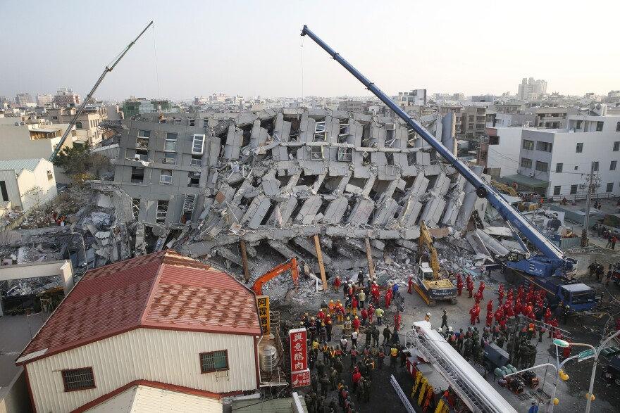 In the early morning, emergency rescuers continue to search for the missing in a collapsed building from Tainan, Taiwan, on Sunday.