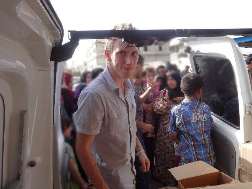 Abdul-Rahman (formerly Peter) Kassig posing with a truck filled with supplies for Syrian refugees.