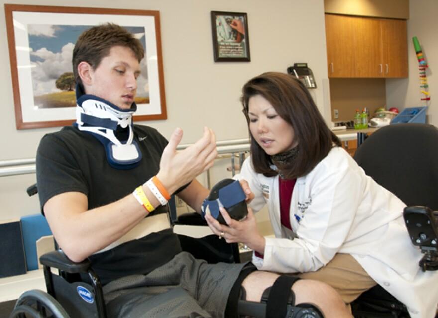 Washington University neurology professor Thy Huskey assists patient Micah Tate at The Rehabilitation Institute of St. Louis.