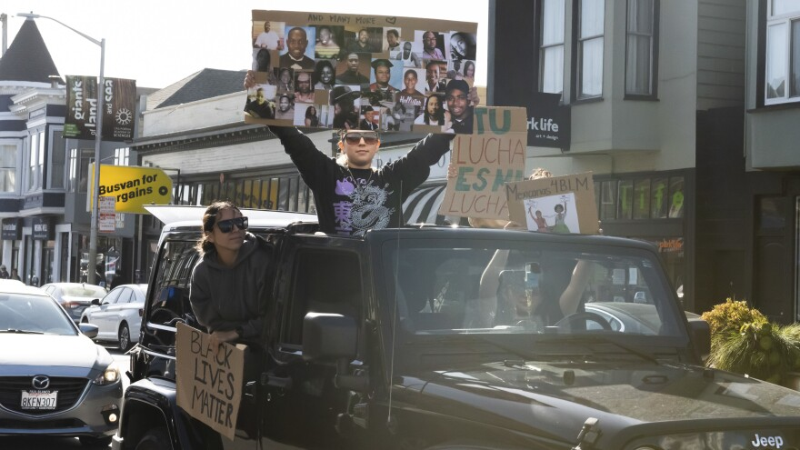 Protesters hold up signs during a caravan protest for justice in San Francisco on Thursday.