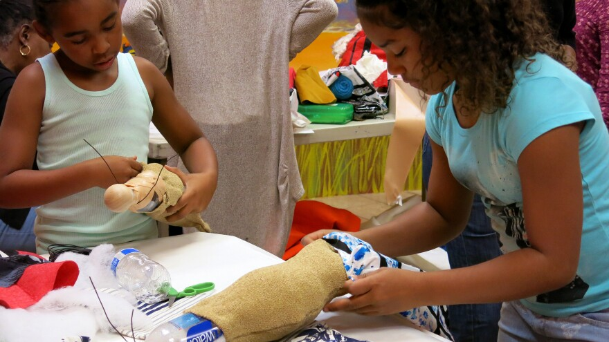 Jesi Russell (left) and Destiny Hill participate in the doll making workshop at the The William Grant Still Arts Center's Black Doll Show in Los Angeles.