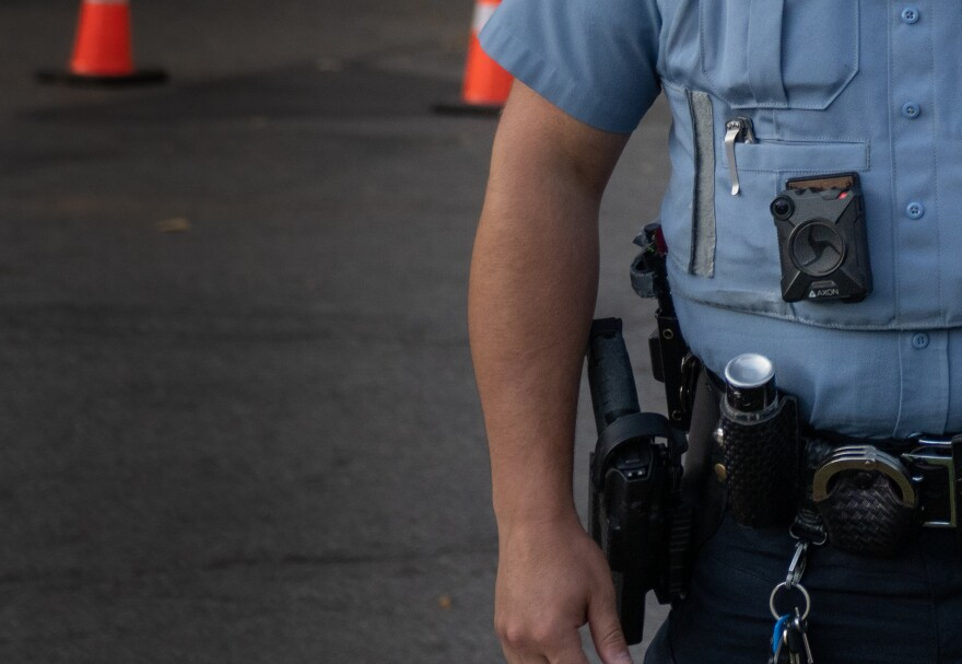 Minneapolis police officer with a light blue shirt wears a body camera.
