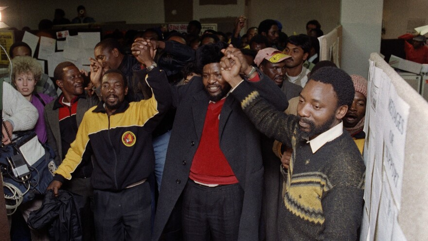 James Motlatse, center, head of the National Union of Mineworkers, and Cyril Ramaphosa, right, general secretary of the union, join hands in singing the national anthem with miners in August 1987 after union members voted to continue a strike by gold and coal miners until their demands were met. The negotiations brought Ramaphosa to national prominence, and to the attention of Nelson Mandela.