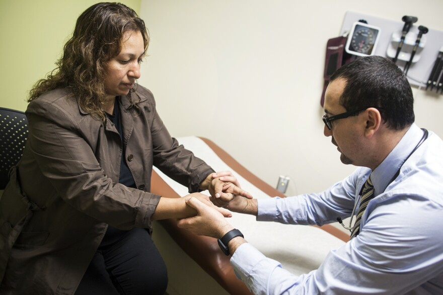 Dr. Cesar Barba (right), a family physician at the UMMA Community Clinic's Fremont Wellness Center in South Los Angeles, treats Lourdes Flores Valdez, 42, for her diabetes and other health issues.