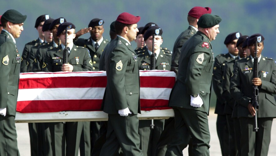 US Army honor guards carry a flag-draped coffin with the remains of Sgt. Gene Arden Vance Jr. from Morgantown, West Virginia, off a C-17 plane at the Ramstein, western Germany, US Air Base, Monday May 20, 2002.