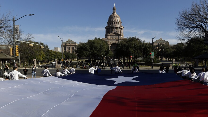 A large Texas flag is carried up Congress Avenue toward the Texas Capitol during the annual Boy Scouts Parade and Report to State in Austin in February 2013.