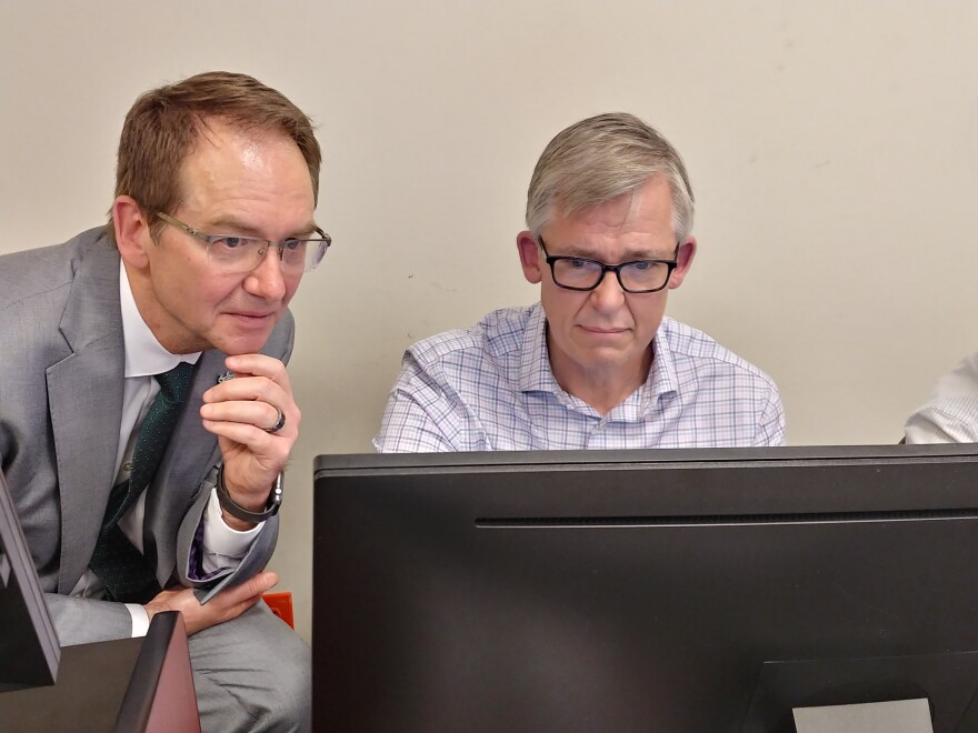Two men with glasses look at a computer screen
