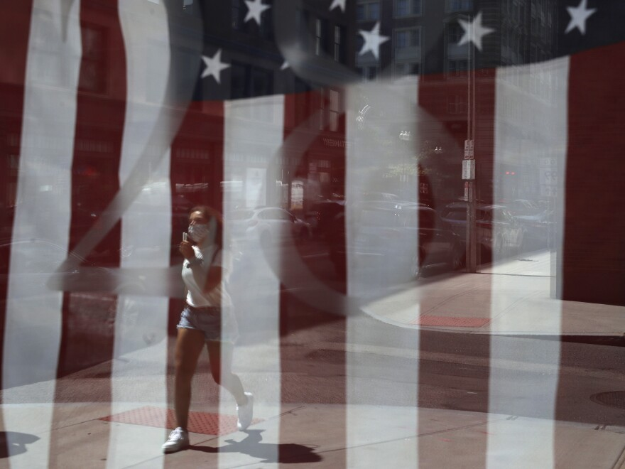 A passerby wears a mask out of concern for the coronavirus while walking past an American flag displayed in Boston on Tuesday. The U.S. has now recorded more than 3 million confirmed cases of the coronavirus.