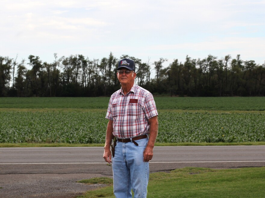 Jimmy Piercey stands outside a deteriorating line of trees meant to protect farmland like his own from dust storm destruction.