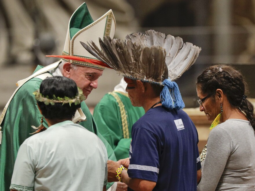 Indigenous peoples, some with their faces painted and wearing feathered headdresses, stand by Pope Francis as he celebrates an opening Mass for the Amazon synod on Sunday.