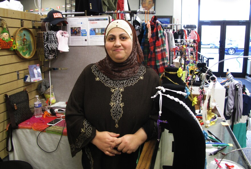 "Nadeen Yousef in her booth, Macrame by Nadeen, at the West Side Bazaar, in Buffalo, N.Y. Yousef moved to Buffalo from Iraq in 2014. ""We are like family here — family from different countries,"" she says."